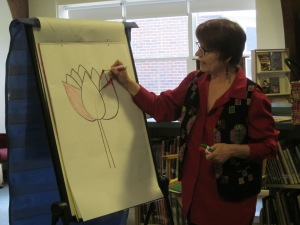 Anne teaching students how to draw a lotus flower, an important symbol in Cambodian culture, at Canal School in Westbrook, ME